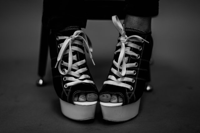 Cropped black and white image of person's feet, wearing black leather peep-toe wedge booties