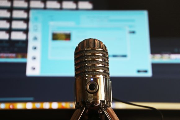 Close up of silver microphone in front of active computer monitor screen