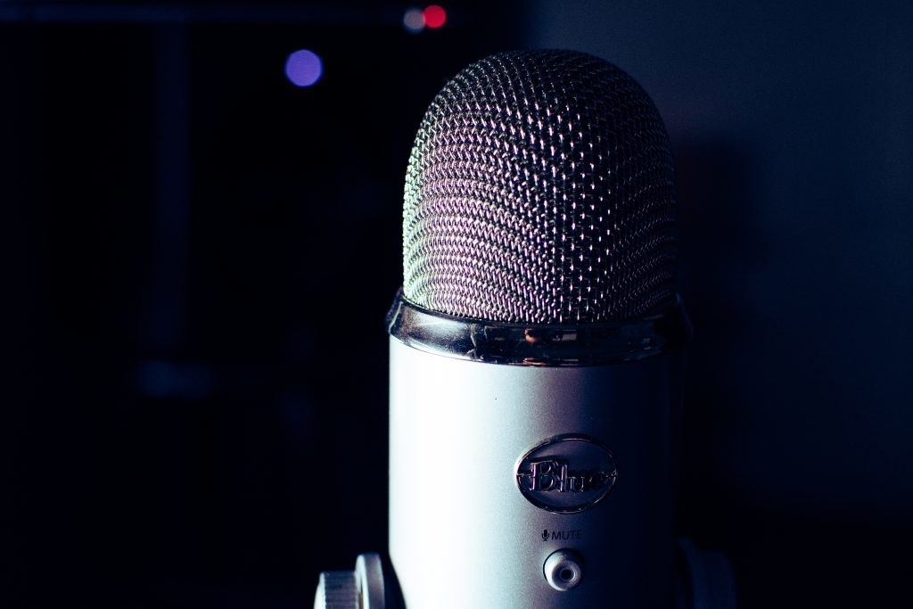 Close up of dark grey coloured  condenser microphone, in front of luminous dark blue background