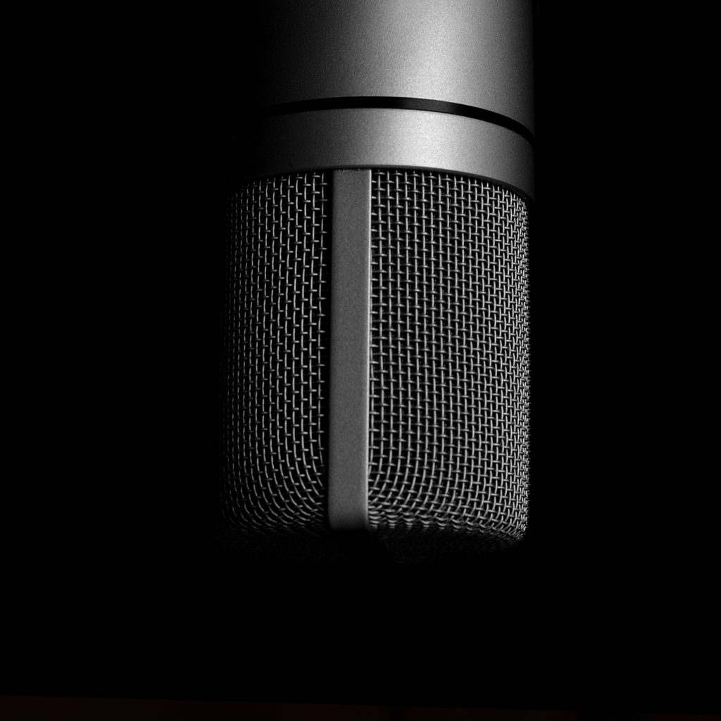 extreme close up of dark grey coloured Condenser Microphone against black background