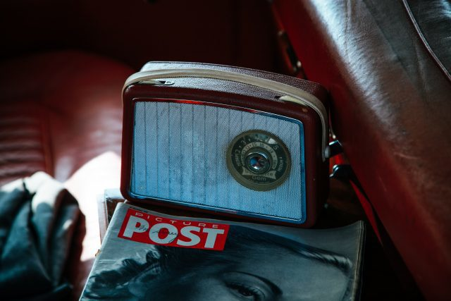 Brown and silver coloured vintage Radio on top of a Picture Post magazine