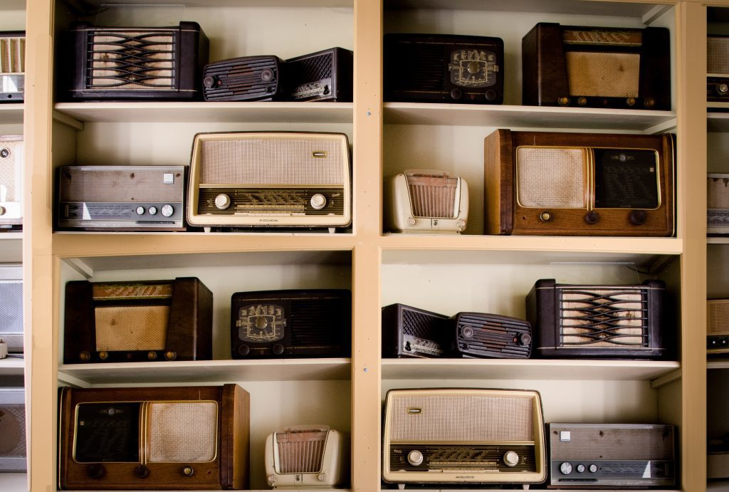 Floor to ceiling light brown book shelf fulled with brown and cream coloured vintage radios