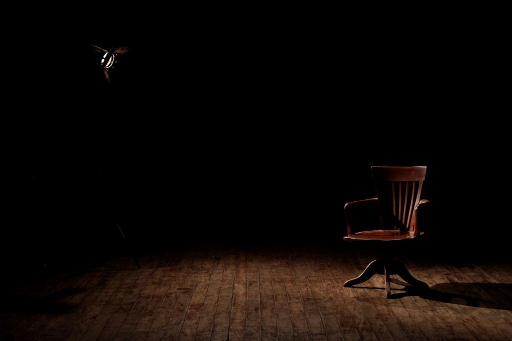 Dark empty room with one soft spot light on a Brown Wooden Armchair on a Brown Wooden Floor
