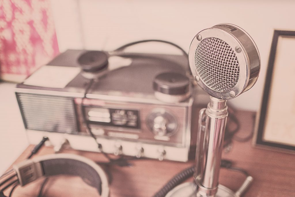 Classic Grey Stainless Steel Cb Radio and vintage microphone on Brown Wooden Table