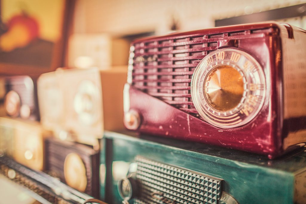 Vintage radio collection is alined and stacked from right to left. From the right, Red coloured vintage radio is in focus, placed on top of a blue coloured vintage radio. Towards the left cream and brown coloured vintage radios are out of focus.