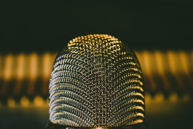 Warm gold tone lighting reflecting on extreme close up of steal microphone