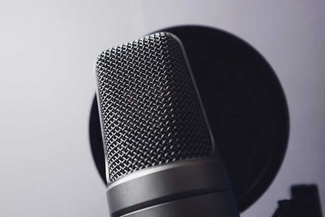 Grey tone image of Silver Condenser Microphone, in front of wind pop filter